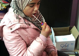 A young woman provides a DNA sample via cheek swab. She was among a cohort of Syrian adolescents forcibly displaced by conflict to participate in a study on the effects of genetic and resilience on the mental health recovery. (Photo courtesy of the research team.)