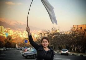 A young Iranian woman waves a white headscarf
